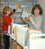 Jan Perkins (left) and Kay Stine, librarians in the children's department of the Huntington City-Township Public Library, move children's books to their new shelves in the expanded library on Wednesday, Feb. 17.