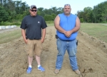 "Tom Wuensch (right), owner of TW Excavating and an Andrews Vounlteer Firefigher, and his son Trey stand in the five-foot pit that the custom ""hot trucks"" will drive through for the Andrews Mud Bogs on Aug. 20."