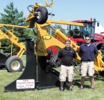 Aaron Hacker (left), sales manager at Elite Ag Solutions, and Cale Eckert, a sales and customer service representative with the company, stand in front of two Johnson Drainage Plows. The plows are a new line carried by Elite Ag Solutions.