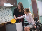 Chelsie O'Neill (left) and Taira Fischer (right), third-year Huntington University occupational therapy doctorate students, are demonstrating hand-over-hand graded assistance in a homemaking task.