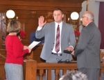 Kevin Rhoades (center) is sworn in on Thursday, Dec. 22, as a full-time officer on the Huntington Police Department by Huntington Clerk-Treasurer Christi McElhaney (left). Rhoades' father, Tom Rhoades (right), holds the Bible for the ceremony.