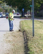 Bill Lesh works on a curb on West Park Drive which has not been cleaned in several years.