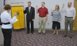 Darlene Stanley (left), outgoing president of the Optimist Club, swears in club officers for the 2010-11 year.
