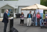 Pathfinder Services President John Niederman (left) speaks during the dedication of three new four-plex supportive living homes for people with developmental disabilities on Tuesday, May 20.