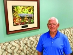 Ed Beckner, a retired pharmacist from Parkview Huntington Hospital, stands next to a photo of a bench with fall leaves he shot that is on display at the hospital. PHH is issuing another callout for photos taken in Huntington County to add to its collection.