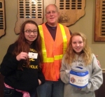 Knights of Columbus Pitch-In Co-chairman Tim Godfroy (center) and his daughters Olivia (left) and Lindsay display items that the volunteers use at the roadblocks including visible vests, collection buckets and pass out cards.