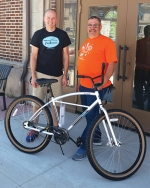 Chris Bucher (left), from Trailhouse Village Bicycles in Winona Lake, and Jim Lewis, HARTA president, display the bicycle that will be provided to the winner of the adult division. Walmart is donating a $50 gift card to the winner of the youth/children division that can be used for a bicycle purchase.