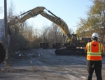Mayor Brooks Fetters, working with the aid of an experienced machinist, operates a backhoe to begin the demolition of the former H.K. Porter Brake Manufacturing Plant on Friday, Nov. 14.