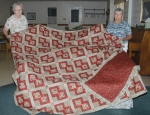 Heritage Pointe of Warren sewing room volunteers Ruth Herring (left) and Janice Ryan display a queen-size quilt and matching pillow covering that is being offered by silent bid auction to raise funds for the volunteer items the group makes for several area hospitals, which include breast pillows and port pillows for cancer patients, veterans' lap quilts and dolls and teddy bears for pediatric units.
