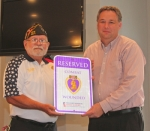 Larry Jenks (left), commander of the Markle Veterans of Foreign Wars Post 6671, presents Markle Town Council President Jeff Humbarger with a reserved parking sign for Purple Heart recipients at the town council meeting on Wednesday, Aug. 17.