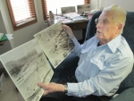 """Bill Jones, a resident of Heritage Pointe of Huntington, looks at copies of some of the aerial photos he took of Hiroshima showing the destruction of the city by the atomic bomb dropped by the United States during World War II. Jones' story is included in a new book by Bluffton author Kayleen Reusser, """"They Did It for Honor: Stories of American WWII Veterans."""""""