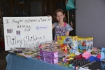 Kaylee Small displays some of the toys, cash and beverage can tabs she collected for Riley Hospital for Children.