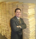 Indiana Secretary of State Todd Rokita poses alongside eight-foot stacks of folders that held corporate documents before being digitally scanned as part of his office's e-Services initiatives.