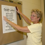 Cindy Crist, sixth grade language arts and social studies teacher at Crestview Middle School, hangs up a poster in her classroom on Thursday, Aug. 6, in preparation for the new school year.