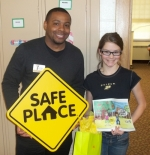 Taylor Vetor (right), a fourth-grade student at Roanoke Elementary School, displays her winning page in the recent Youth Services Bureau's annual Safe Place Coloring Contest. With her is Safe Place/Host Home coordinator Steve Ward.