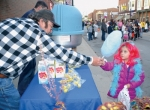 Everett Davis (left), working the UAW Local 2209 booth, hands a stick of cotton candy to a costumed Emoree Jones during the 2016 Scarecrow Festival in downtown Warren. The festival will be held again on Friday, Oct. 27.