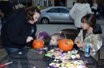 Kaitlyn Boxell (left) helps Olivia Bailey (center) decorate a pumpkin while Gabbi Keene looks on at the booth of Mike and Stacy Haggerty during the 2013 Scarecrow Festival in Warren on Friday night, Oct. 25, 2013.