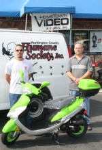 "Anthony Wilson (left), chairman of the Huntington County Humane Shelter's ""Waggin Tails, Doggie Trails' on Oct. 10, and James Wagner, Hometown Video owner, are shown with a scooter to be given away at the event. Hometown is the sponsor for the scooter."