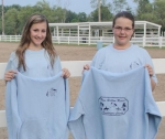 Blue Ribbon Riders 4-H Club members (left) Savanna Stoltz shows off her winning design for the front of the club's new shirts, while fellow club member Kaitlyn Drayer displays her winning design for the back of the shirt.