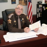 Huntington County Sheriff Terry Stoffel holds a list of just a few of the names of children recommended for the 15th annual Shop with a Cop program by elementary schools and the Department of Family Services. Stoffel says 50 kids will participate this year, partnering with a law enforcement officer to go shopping for Christmas. He hopes community donations will help fund the program.