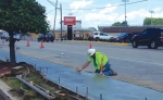 A worker smoothes concrete on a new sidewalk alongside Jefferson Street during recent improvements. City residents and business owners can get some financial help from the City of Huntington to replace damaged sidewalks with new walks.