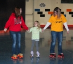 Khloe Rees (middle) holds hands with Jewel Shively (left) and Stephanie Johnson as the trio ventures out onto the rink at West Park Skate Center, in Huntington, during a benefit for Wyatt Schmaltz, a local 3-year-old being treated for cancer.