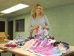 Chris Walker, executive director of the Indiana Dream Center, shows just a few of the new athletic shoes that will be given away during the 10th annual Steps for Success celebration set for Wednesday, Aug. 7, at The Awakening Church, in Huntington.