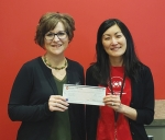 Marcy Hawkins (left), Huntington University's director of alumni relations and director of the Forester Fund, accepts a donation from Gwen Burns, service center manager at the Huntington Teachers Credit Union.