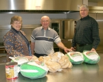 Jean Hayden, food chairman; Jim Wilson, general chairman; and David Ballinger, pastor at Trinity United Methodist Church (from left) are pictured with some of the food items that will be served during this year's community Thanksgiving dinner.