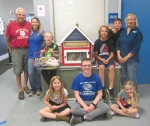 "Members of the Parkview Boys & Girls Club of Huntington County celebrate their new ""tiny library,"" recently donated by the Professional Piddlers group. The Huntington Habitat for Humanity ReStore donated books to the library. Celebrating the occasion are (front row from left) Cheyanne Carpenter; Brant Shelby, a staff member at the Club; and Serenity Sadler; and (back row from left) Stan Bippus, of the Professional Piddlers; McCall Burnau, from the ReStore; club members Tristan Mitchell, Rylan Finley and Caden Douglas; and Jo Burnau, manager of the Huntington ReStore."