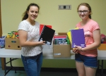 Youth Services Bureau staff member Bethany Brunner (left) and volunteer Emily Mead show some of the school supplies they are collecting for the agency's Tools for Life program.