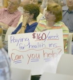 Sylvia Kaufman (front right) of Huntington, makes her feelings known with her sign as she listens to Tep. Dan Burton discuss healthcare reform at a town hall meeting at Flint Springs Elementary School on Thursday, Aug. 27.