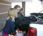 Crestview Middle School students (from left) Kylie Frederick, Chloe Spencer and Stephanie McElhaney load a pickup truck with supplies to be taken to the Huntington County Humane Society on Friday, Feb. 19. The girls collected thousands of items.