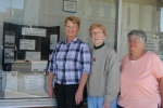 Huntington County Extension Homemakers members Kate Nave, Glenna Brown and Edie Fulton (from left) stand next to the downtown business window they decorated in observation of Extension Homemakers Week.