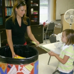 "Morgan Murray, 6, is assisted by Jennifer Mihalec, a summer intern at the Youth Services Board, as Murray donates school supplies to the YSB's ""Tools for Life"" program. Several collection points for school supplies are located around the county."