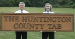The Huntington County TAB co-owners Russ Grindle (left) and Scott Trauner hold the original sign they made to put over their first location at 1751 B N. Jefferson St., Huntington, when they started the newspaper 25 years ago.
