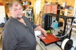 Steve Mitchell shows how his 3-D printer lays a thin layer of plastic at a time to make the fidget spinners he is creating with the machine.