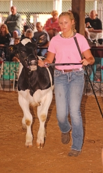 Blake Drasny walks her dairy starter calf inside the Parkview Huntington Hospital Show Arena on July 24, 2019, during last year's Huntington County 4-H Fair. Drasny's calf took champion honors.