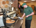 On the job, Zachery Arivett wipes down the pizza counter in the dining commons at Huntington University during lunchtime on Wednesday, March 1. Arivett participates in the ABLE program, a partnership between HU and Huntington North High School for students with mild to moderate cognitive disabilities.