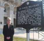 "Huntington County Bar Association President Amy Richison stands with the sign the association had redone outside the Huntington County Courthouse, which celebrates the landmark ""Ex Parte Milligan"" Supreme Court ruling involving a Huntington attorney."