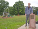 "Rick Wright stands next to the new drinking fountain at the Andrews Park that pays tribute to his late wife, Linda Wright, who was the leading force in the rehabilitation of the once-neglected park. A plaque attached to the fountain notes that Linda Wright ""believed that public places are what tie a community together,"" prompting her to work for the restoration of green space and playground equipment seen in the background."