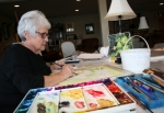 Using a photo as her guide, Roanoke artist Cherie Droege works on a still life painting in her home studio in rural Huntington County. She has been painting, mostly using watercolors as her medium, since she was a child.