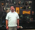 Huntington University professor and Huntington resident Tanner Babb stands in front of some items on display at the Huntington City-Township Public Library from the Harry Potter collection he and his wife Julie have.