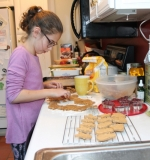 Evie Webb, 10, of Huntington, uses Christmas-themed cookie cutters to shape her dog treats she will then bake and sell. The proceeds from her project go to help build earthquake-resistant houses in Haiti.