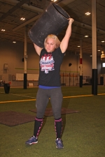 Christina Bangma, an amateur strongman from Huntington, heaves a keg of steel into the air during a recent training session at Champs Academy. Bangma will be participating in the Arnold Amateur Strongwoman World Championships at the Arnold Sports Festival in Columbus, OH, which runs from today, Thursday, March 2, through Sunday, March 5.