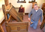 Jack Oberholtzer (back) and Rev. Bob Land reassemble the wooden apparatus containing the levers originally used to play the chimes at Trinity United Methodist Church. A men's group from the church brought the apparatus down from the bell tower and reassembled it on the church's balcony level, where it will be on display for the celebration of the 100th anniversary of the chimes' dedication.