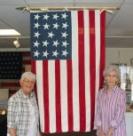 Jo DeFord (right) stands beside the 19-star U.S. flag she created and sewed, along with Roanoke Area Heritage Center Secretary Sharon Williams, inside the center on Thursday, Sept. 22. The flag was flying at the time Indiana became the 19th state of the Union in 1816. DeFord's flag will be displayed at Roanoke's bicentennial celebration on Friday, Sept. 30.