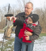 Hunter Saunders (right) gets a little help from his grandfather, Rick Saunders, as they fill the bird feeders in the back yard of Rick's residence in rural Andrews. Hunter is credited with being able to identify nearly 80 birds.