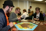 "Huntington University students (from left) Nick Berry, a freshman from Fort Wayne; Nick Beery, a freshman from Fort Wayne; and Stormie Thorn, a freshman from Wayne, OH, set up the pieces of the board game Settlers of Catan during class time Wednesday, Jan. 14. The game is part of the curriculum of the ""Learning to Think Strategically"" class taught by psychology professor Tanner Babb."