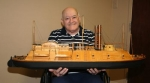 L.D. Williams, of Huntington, holds the USS Cairo, one of 25 boats he has handcrafted over the years. Williams recently had an exhibition of some of the vessels at Miller's Merry Manor.